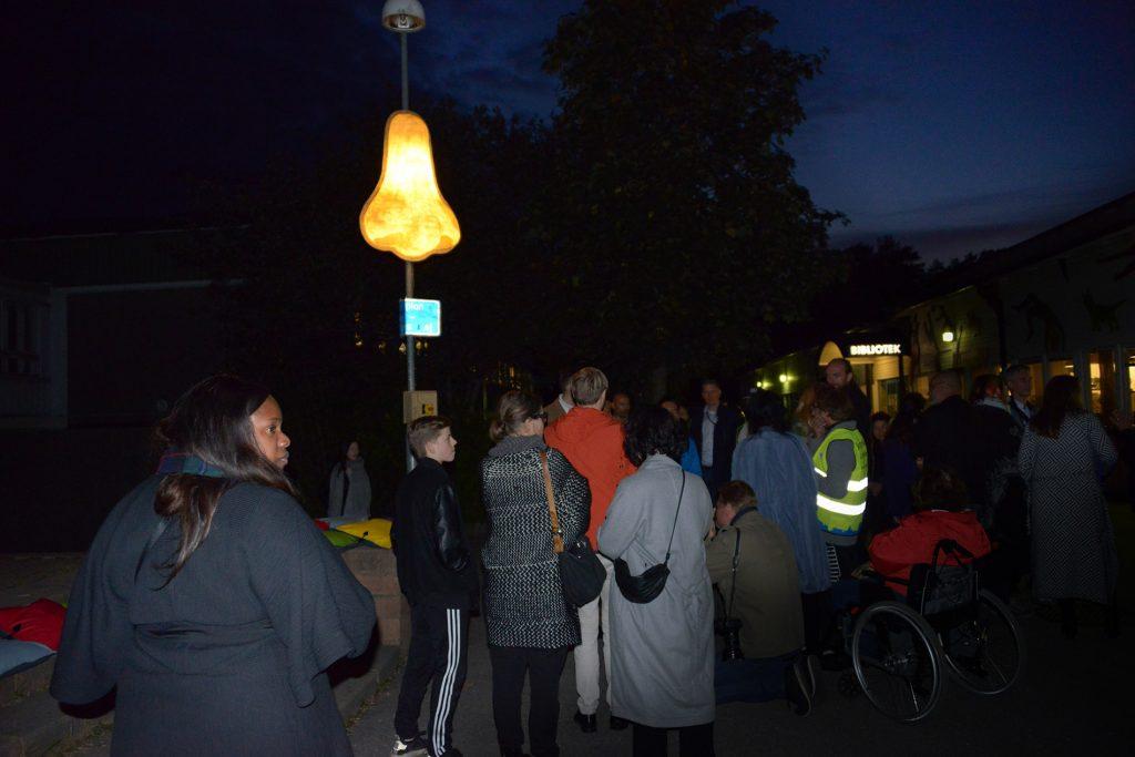 Människor står framför kulturhuset, vid den lysande näsan som sitter på en lyktstolpe, det är mörkt och bilden är tagen med blixt.