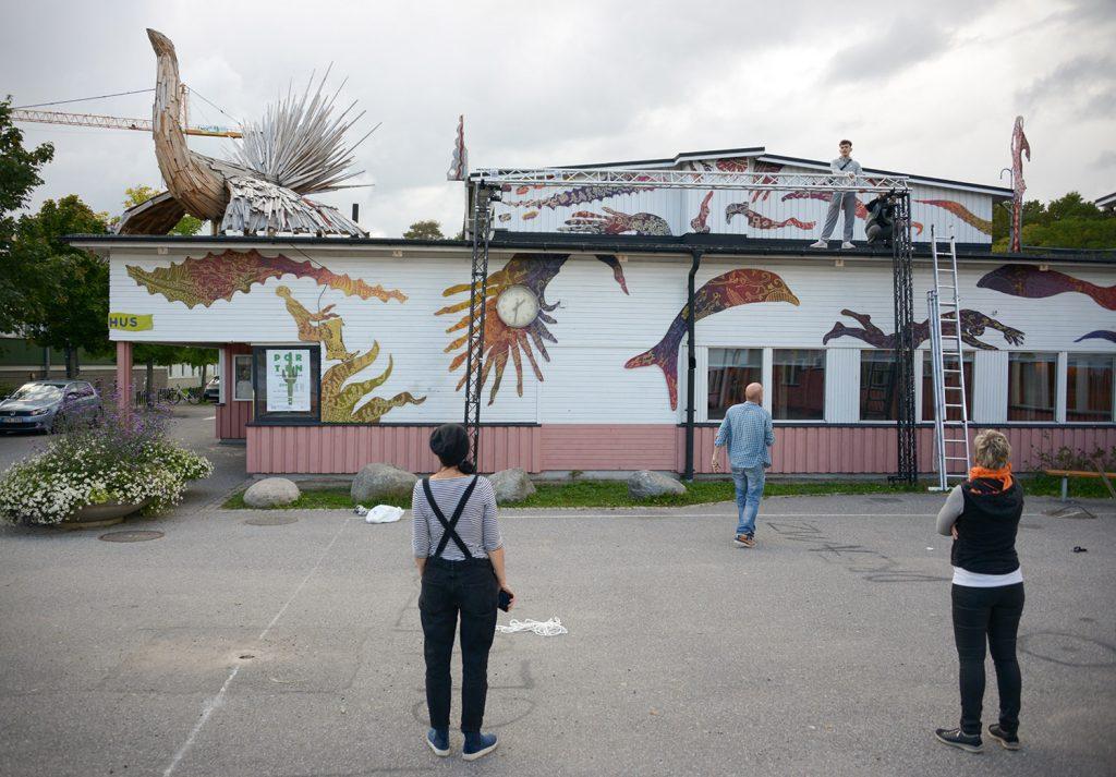 Utanför kulturhuset i Jordbro förbereds, en tross sätts upp på fasaden som ska hålls en filmduk vid invigningen.