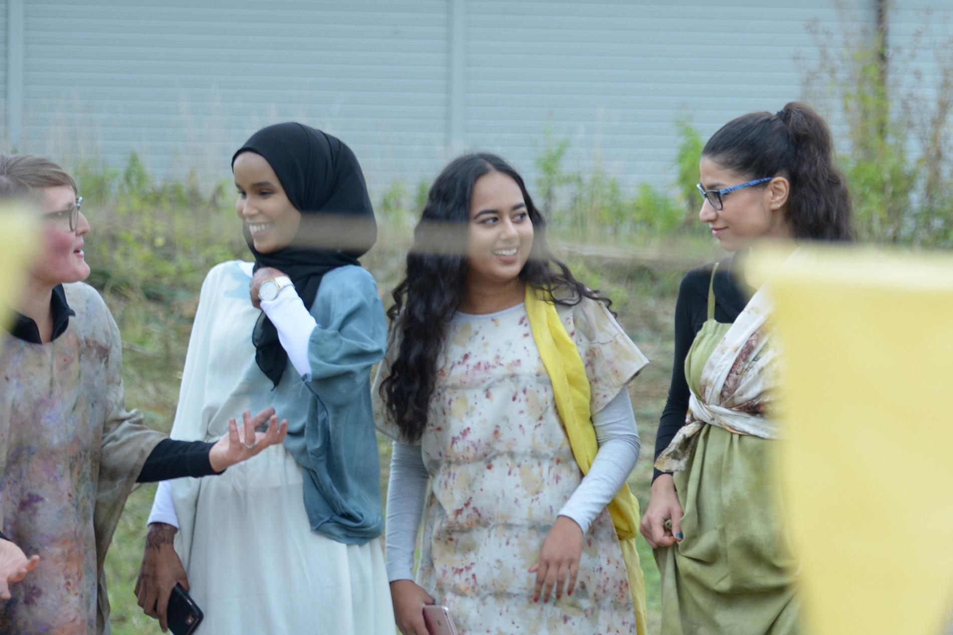 Fyra personer står i förgrunden och har på sig kläder som färgats under Konst händer-workshops. I bakgrunden grönt gräs.