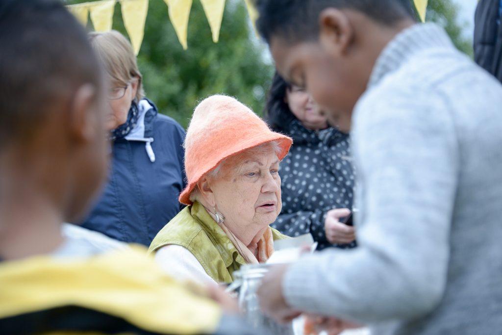En av deltagarna sitter ned vid ett färgningsbord, hon har en orange tovad hatt och en grönfärgad väst.