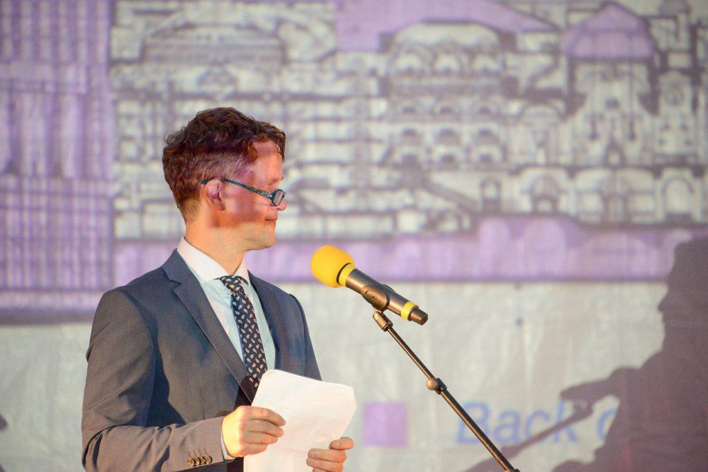 Per Sternbeck står på scenen, i ljuset av en projektion.