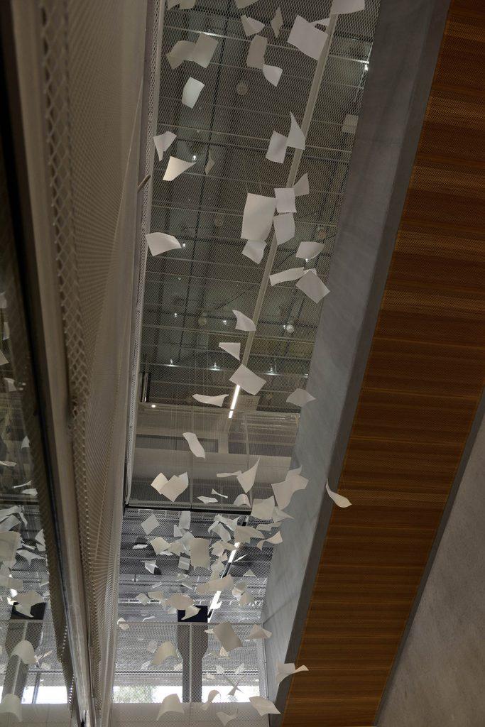 Virvlande pappersark i luften bredvid trappan. Gabriel Lester, Twirl, 2013