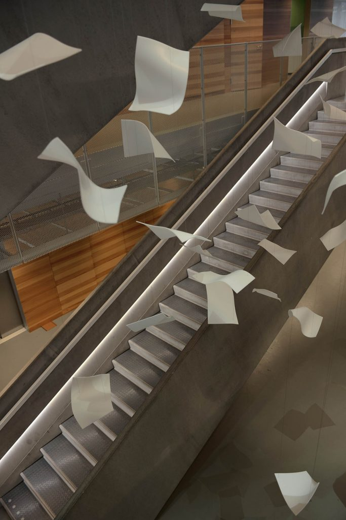 Virvlande pappersark i luften ovanför trappan. Gabriel Lester, Twirl, 2013