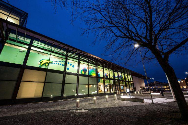 Polishusets glasfasad utifrån i nattmörker. Innanför på den upplysta väggen syns delar av det trettiofem meter långa färgglada verket. Anna Svensson, Tillsammans.