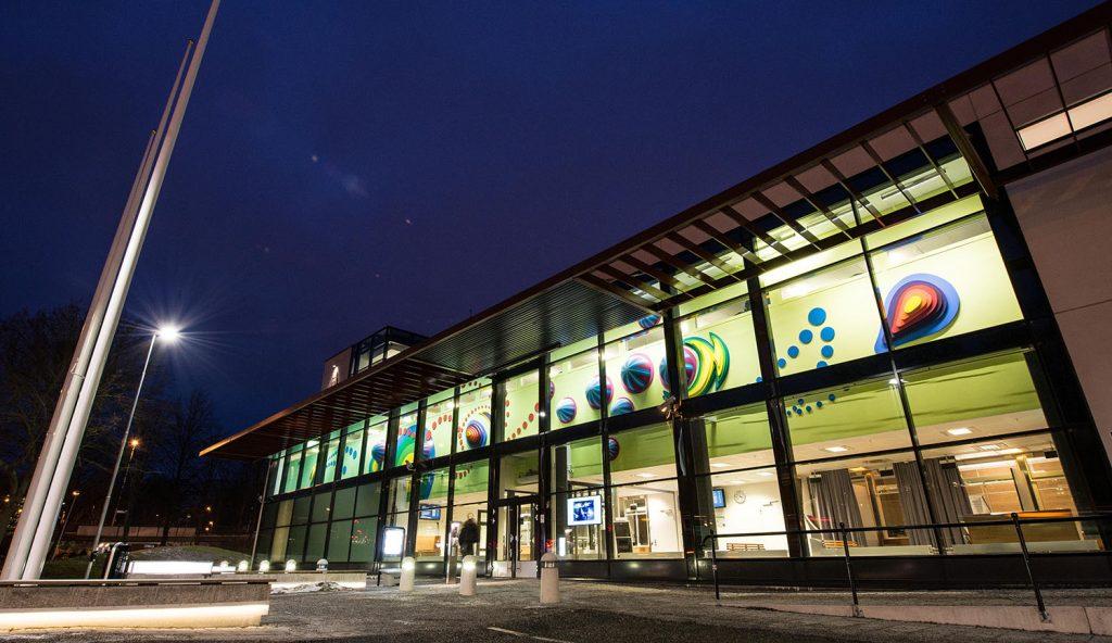 Polishusets glasfasad utifrån i nattmörker. Innanför på den upplysta väggen syns delar av det trettiofem meter långa färgglada verket. Anna Svensson, Tillsammans