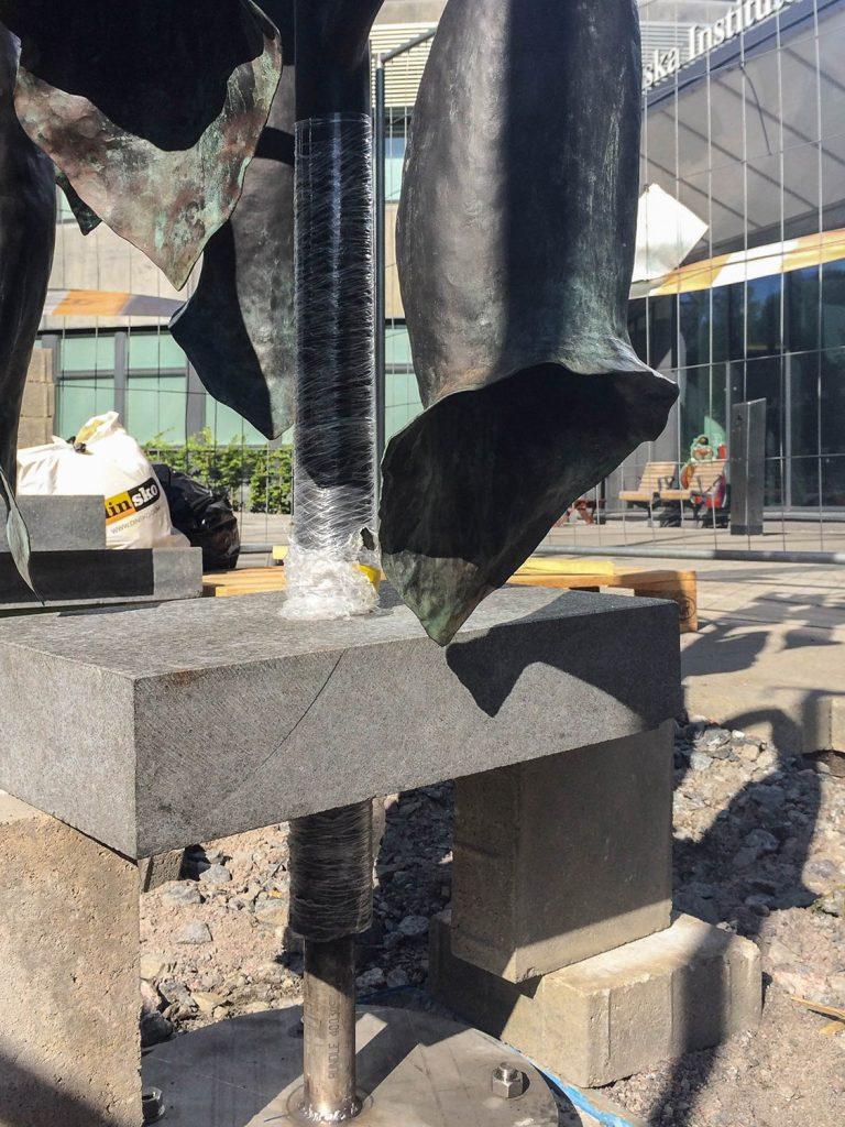 Framför entrén finns en fingerborgsblomma i brons vars smäckra men tunga blomklockor lånat kobjällrans kläpp. Thale Vangen, Läckage i oskuldens trädgård, 2014