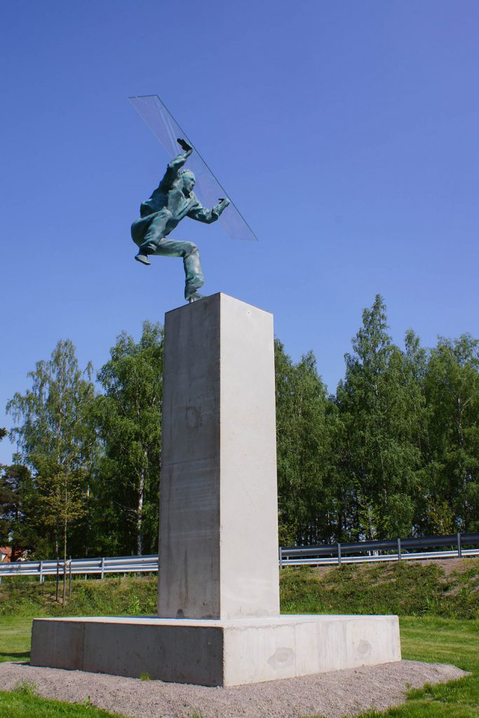 Grönärgad skulptur på en hög stensockel av en man på språng. Han har böjda knän och ena foten i luften. Heinrich Müllner, Flyer, 2014