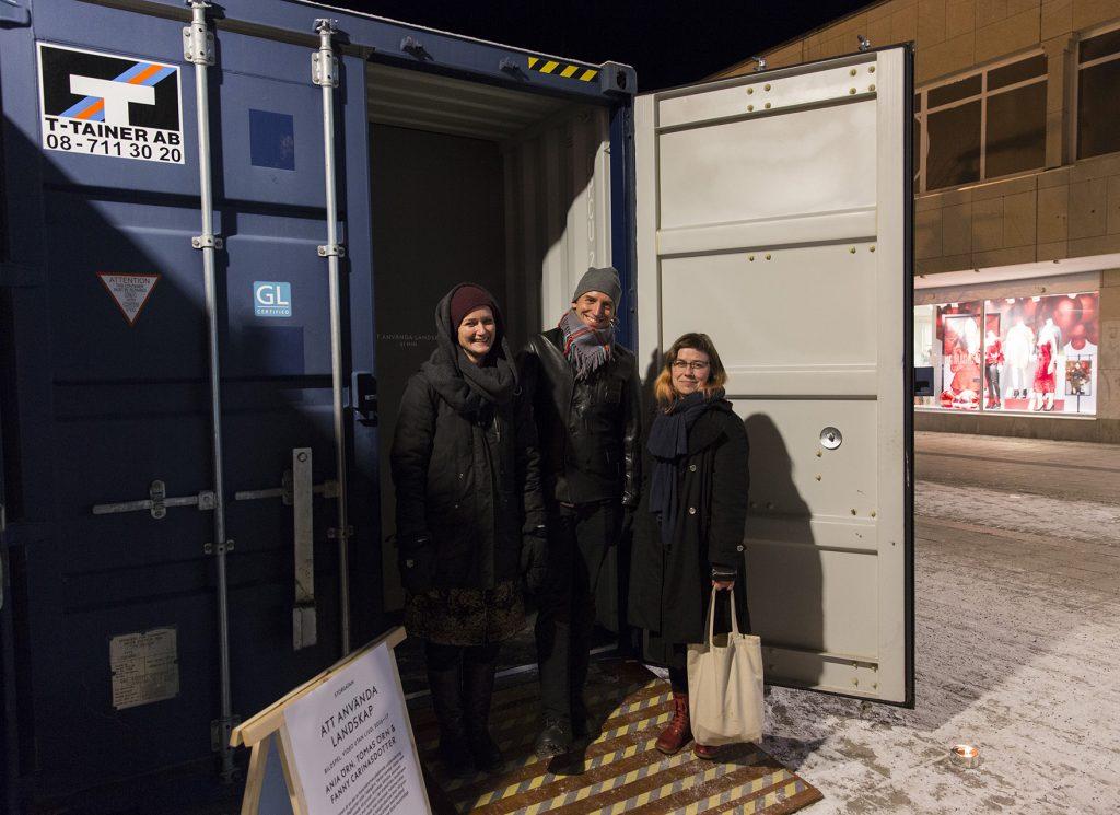 Bild på konstnärerna som står framför en container