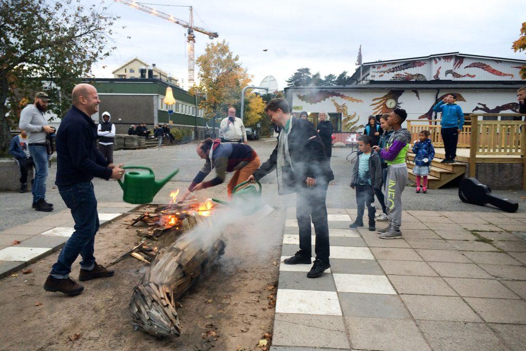Människor står samlade framför en stor träskulptur i delar, vissa delar brinner samtidigt som två personer häller vatten på med gröna vattenkannor.