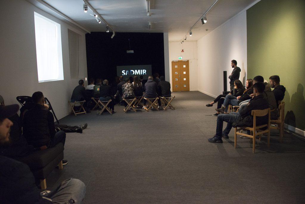 Människor i en museilokal som tittar på film