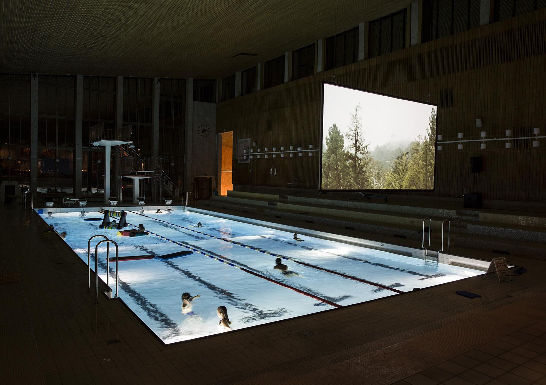 Bild på en stor skärm som hänger över en simbassäng