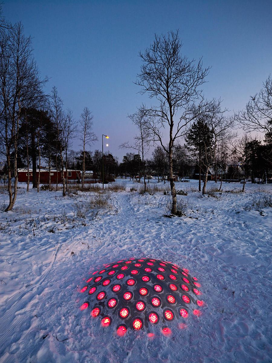 Ur den nedtrampade snön sticker termonoden upp. Lamporna lyser röda i mörkret. I bakgrunden träd och röda byggnader. Markus Lantto, Termonoder, 2009