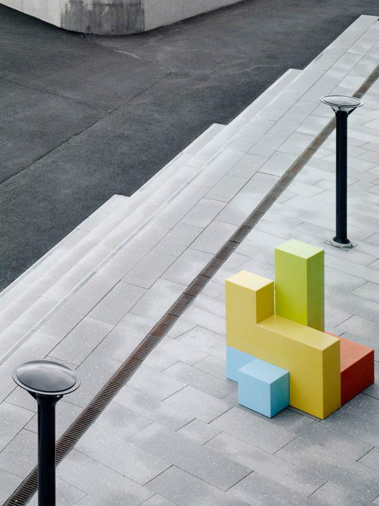 På trottoaren står en grön, gul, orange och blå skulptur. Jacob Dahlgren, Tetris, 2012