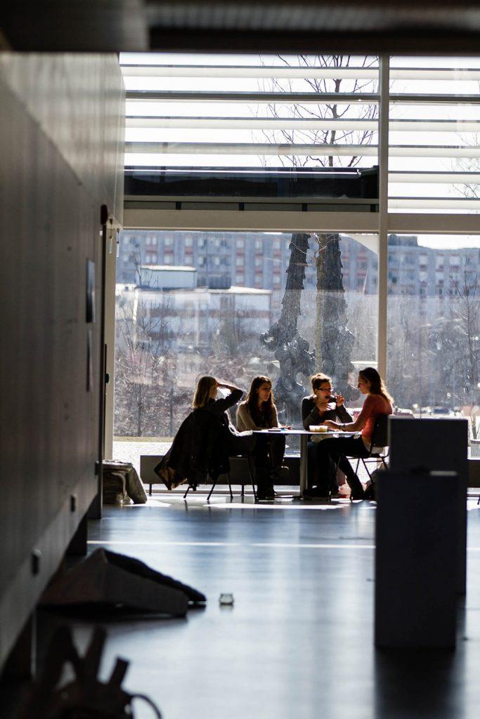 Fyra kvinnor äter vid ett bord. I bakgrunden en glasvägg ut mot gården, där en hög bronsskulptur sträcker sig mot himlen. Carl Boutard, Into The Wild (2013)