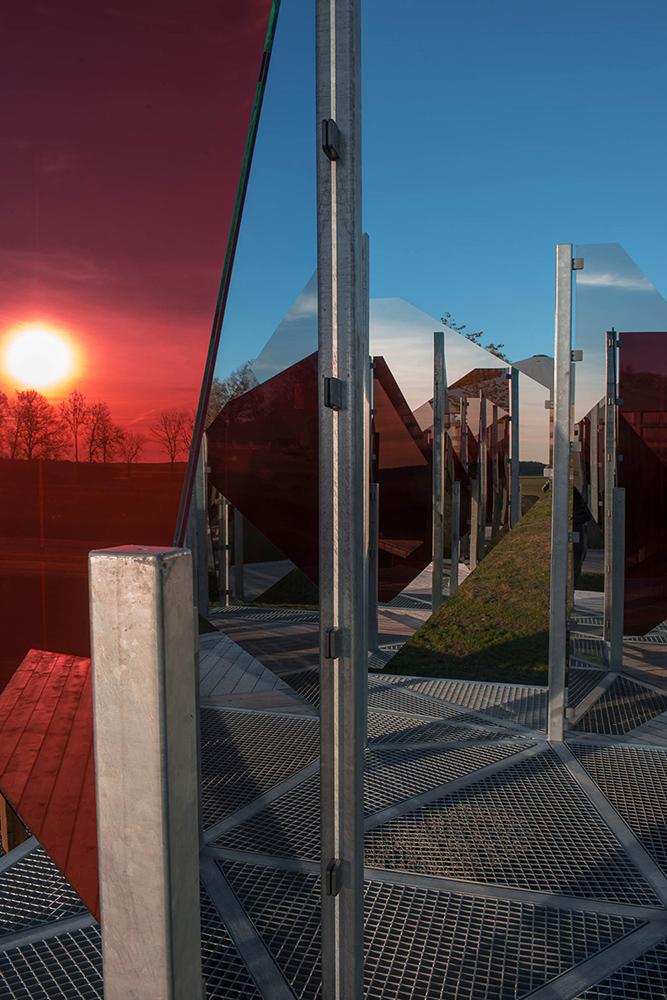 På nära håll skapas en mosaik av speglingar. Även den sjunkande solen fångas av glaset. Patrik Aarnivaara, Tidsglänta, 2013
