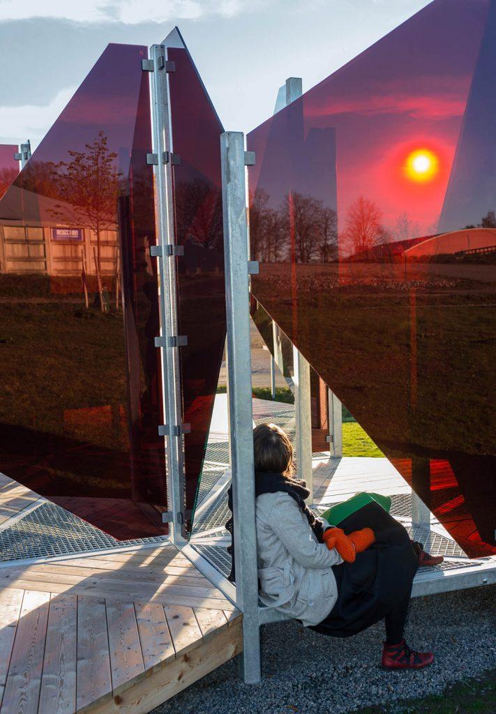En kvinna sitter bortvänd på trägolvet mellan glasskivorna som speglar den sjunkande solen. Patrik Aarnivaara, Tidsglänta, 2013