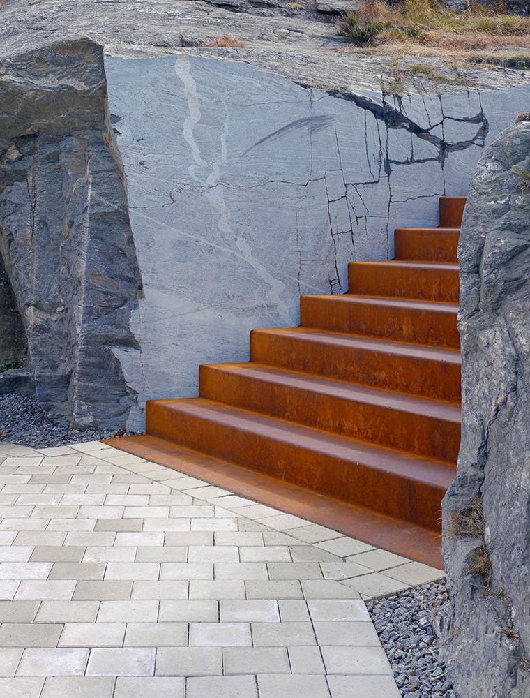 Stenläggning vid foten av den roströda trappan som sänkts ner i klippan. Leo Pettersson och Mia Fkih Mabrouk, Utan titel, 2013