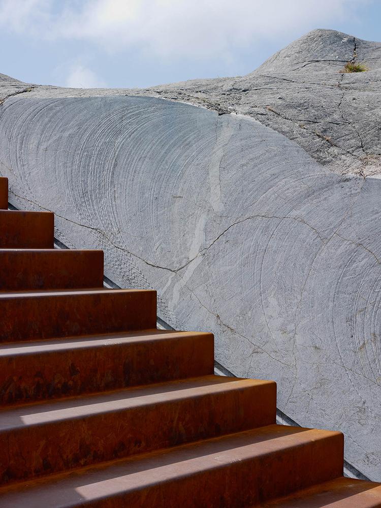 Del av roströd trappa nedsänkt i klippan. Leo Pettersson och Mia Fkih Mabrouk, Utan titel, 2013