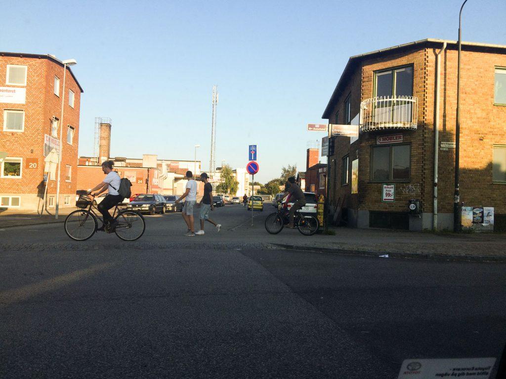 En gatukorsning där en man i vit t-shirt passerar på cykel.