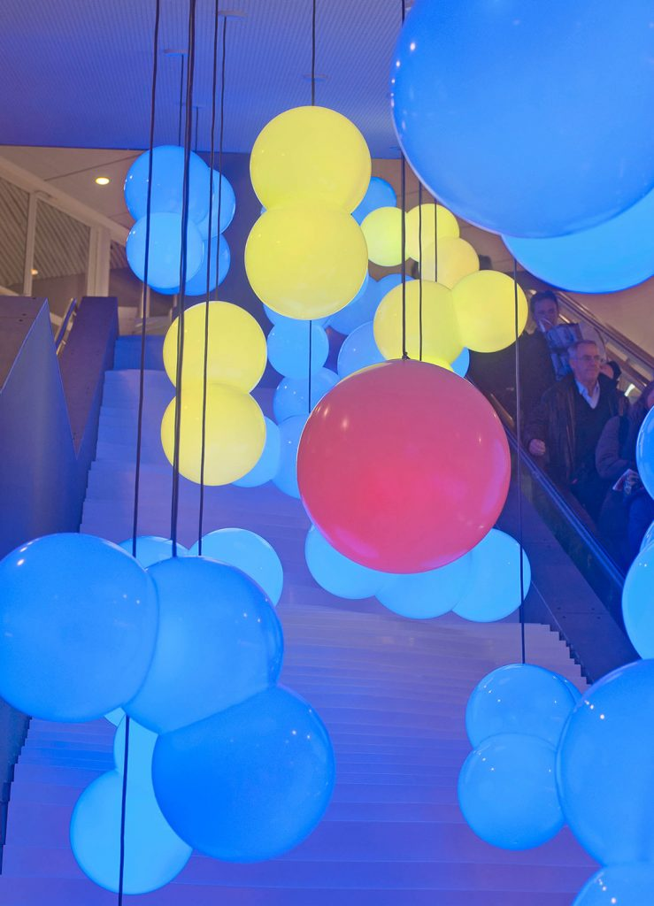 En stor klotrund röd lampa omgiven av några mindre gula och flera blå. I bakgrunden människor som åker i en rulltrappa. Bigert & Bergström, Morgondagens Väder, 2012