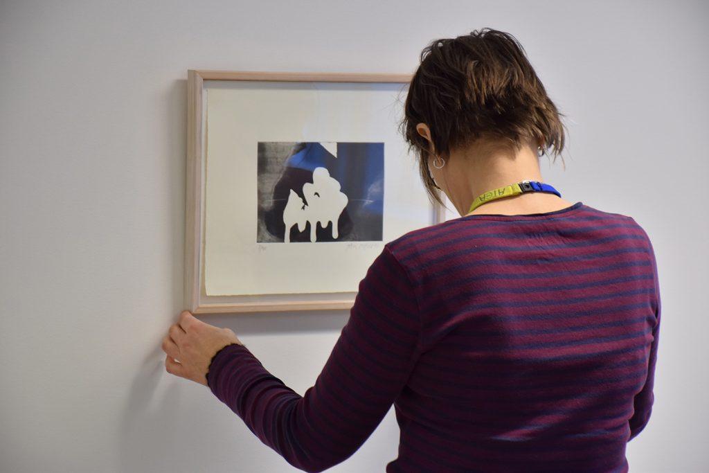 Hanna Stahle hänger ett verk.