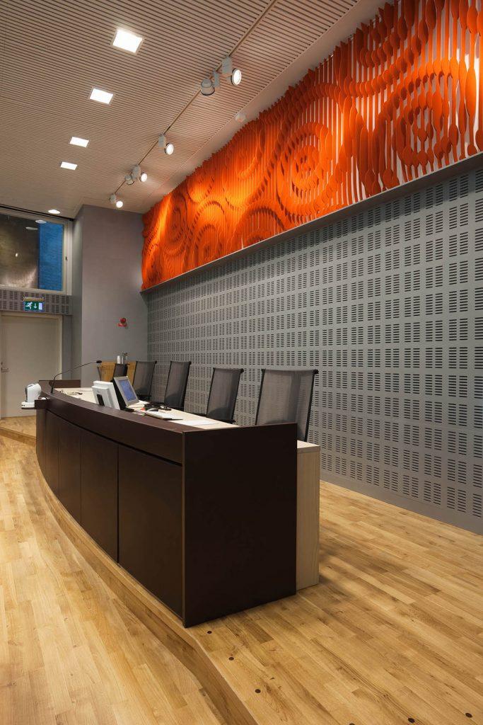 Panel på väggen ovanför domarbordet. Orangefärgad med utskurna spiralliknande mönster. May Bente Aronsen, Lyssnande vägg