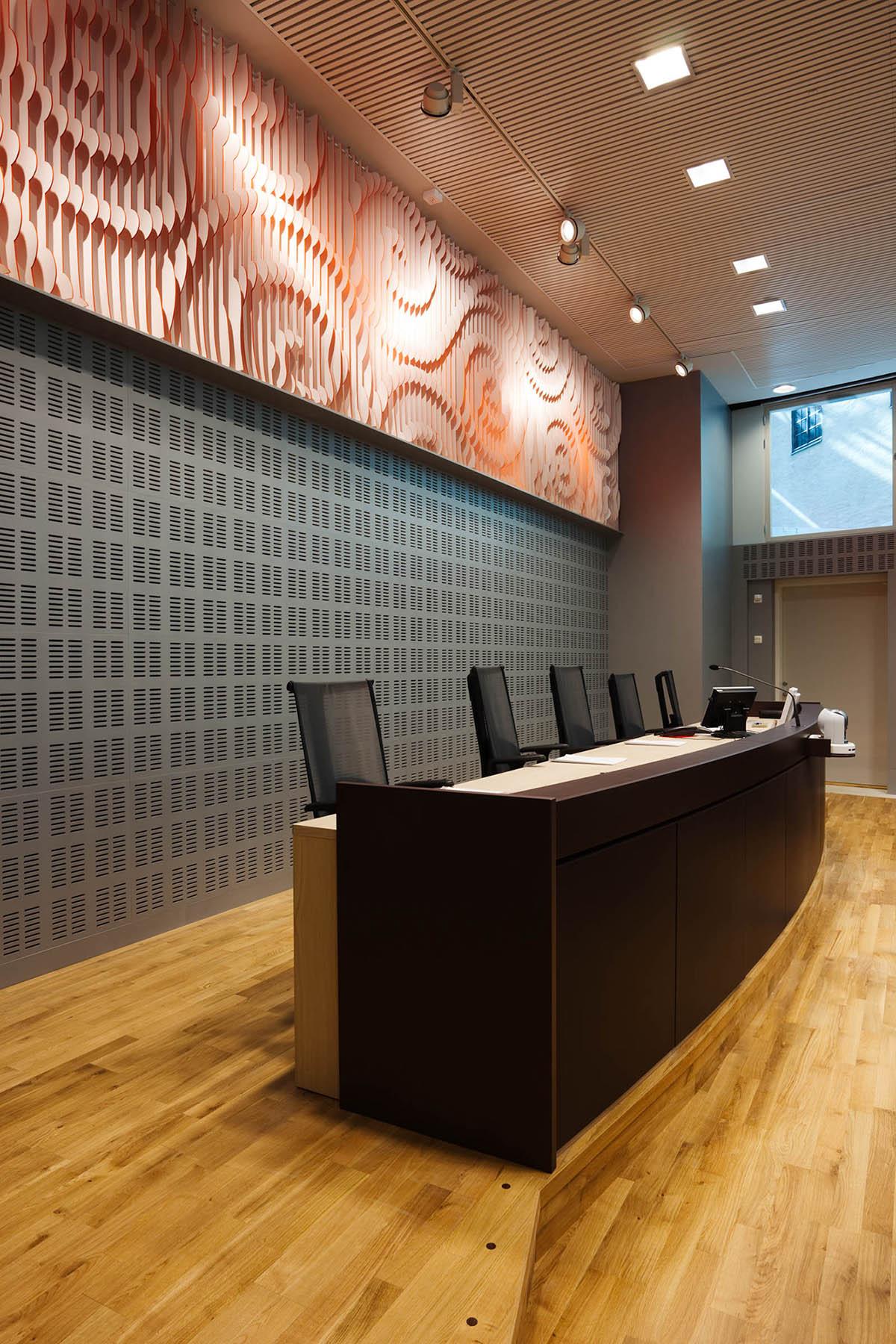 Panel på väggen ovanför domarbordet. Beige-rosa med utskurna spiralliknande mönster. May Bente Aronsen, Lyssnande vägg