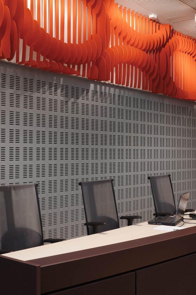 Panel på väggen ovanför domarbordet. Orangefärgad med utskurna cirkelmönster. May Bente Aronsen, Lyssnande vägg
