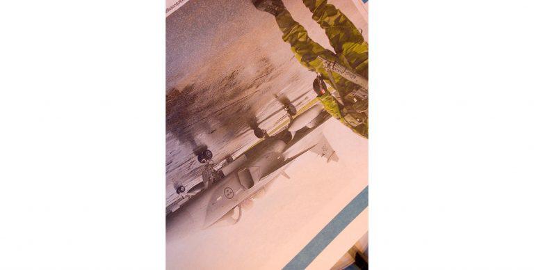 Stillbild ur verket. En del av ett flygplan och någons ben i kamouflagekläder. Bilden är snett upp och ner.