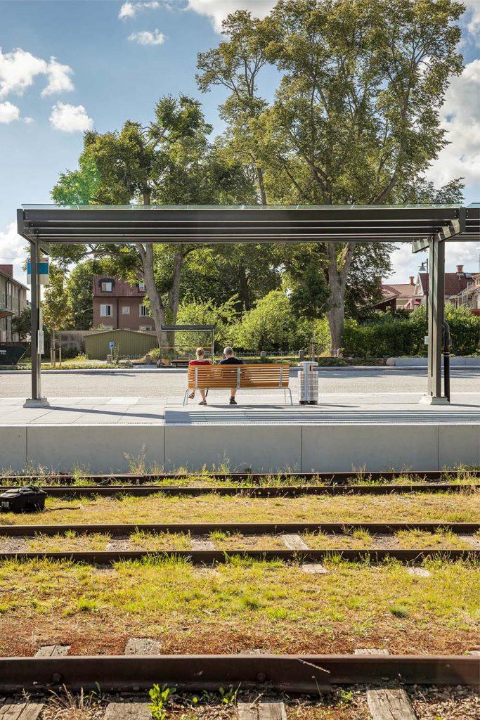 Väntplats utomhus med glastak och bänkar mellan järnväg och asfaltväg. Människor sitter på bänkarna. Magnus Carlén och Karin Tyrefors, Resecentrum i Nora, 2013
