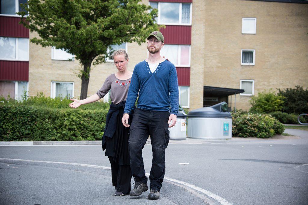 En kvinna leder en blundande man över en parkering i ett bostadsområde. Myriam Lefkowitz, Walk, Hands, Eyes (Gamlegården)