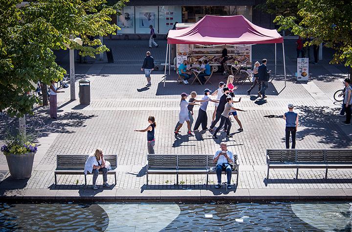 En grupp personer på ett torg med armarna utsträckta. I bakgrunden ett matstånd. Arbetets monument Alexandra Piric