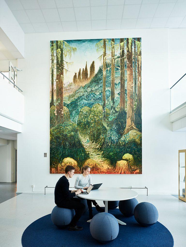 Målningen med den trolska skogen är lika hög som två våningsplan. Nedanför en person i en blå soffgrupp. Danilo Stankovic, När fåglar tystna.