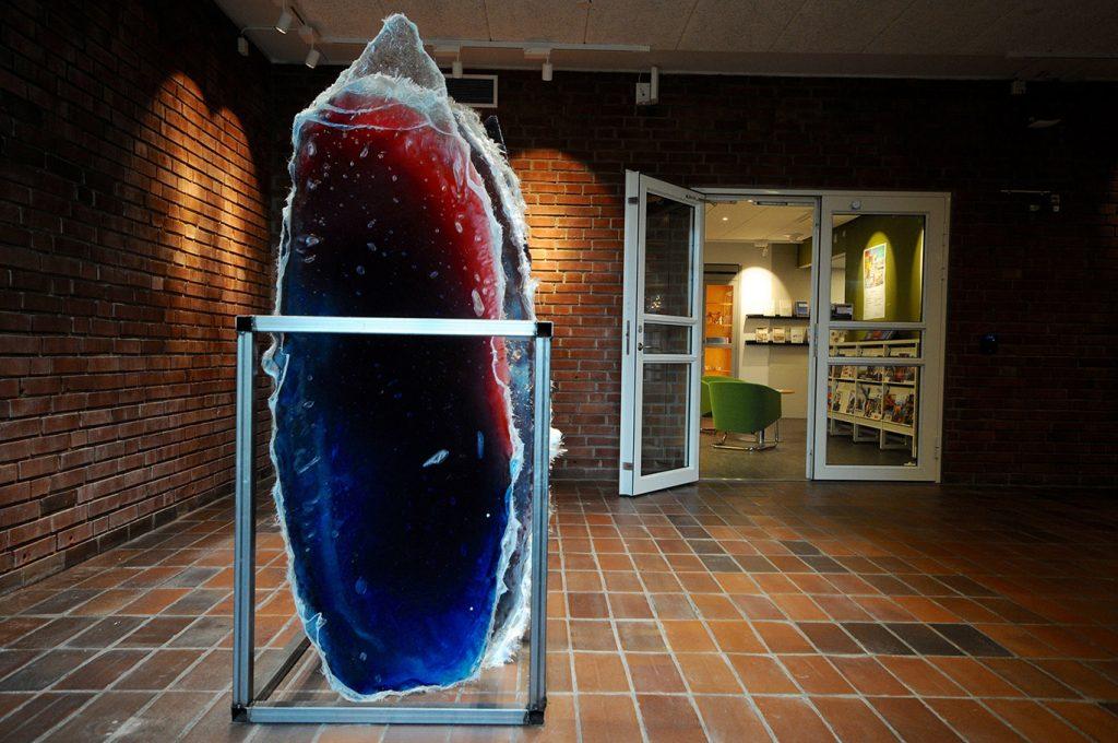 Verket skiftar i olika nyanser av blått och rött, och står uppställt i ett stålstativ. Tiril Hasselknippe, Surfboards (Vattenhuset)