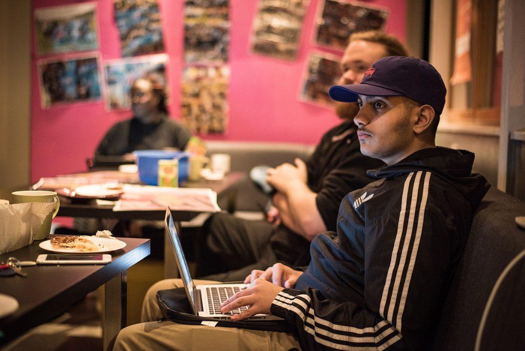 Unga människor i en kaféliknande miljö med mat på bordet och dator i knät, lyssnar på någon utanför bilden.