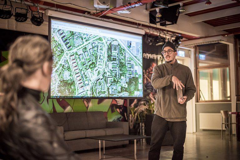 En man står och pratar framför en områdeskarta på en projektortavla.
