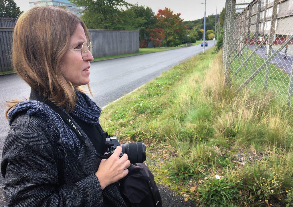 Person i profil vänster i bild som håller en kamera, bilväg grönt gräs och stängsel i bakgrunden.