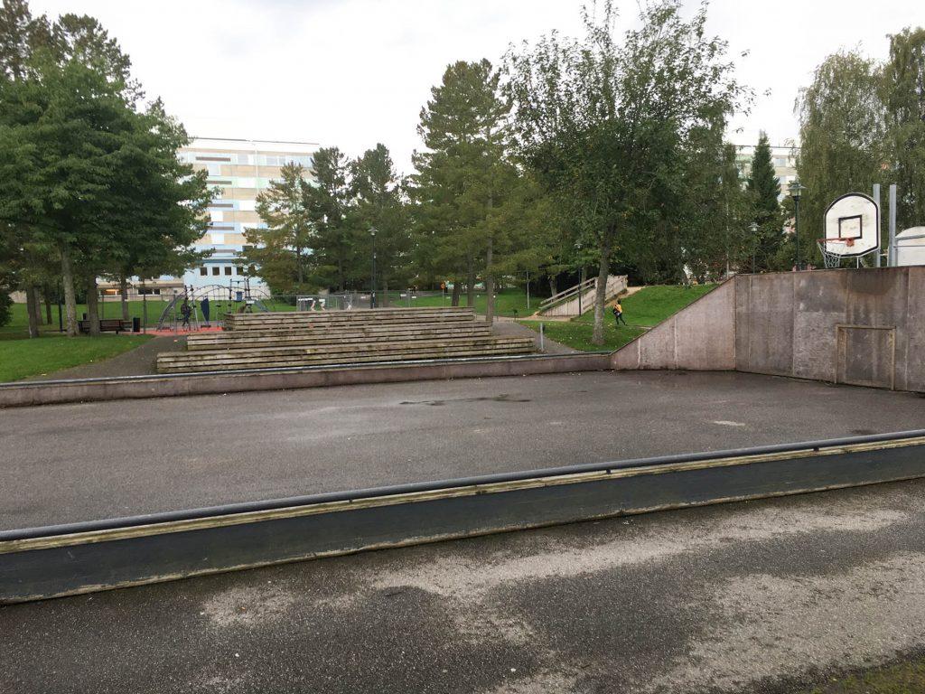 Asfalterad basketplan med lekplats och park i bakgrunden.