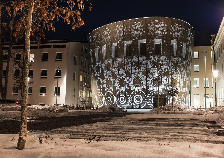 Översiktsbild av en fasad där grafiska former skapar mönster av blommor som också bildar ett vackert ljusspel.