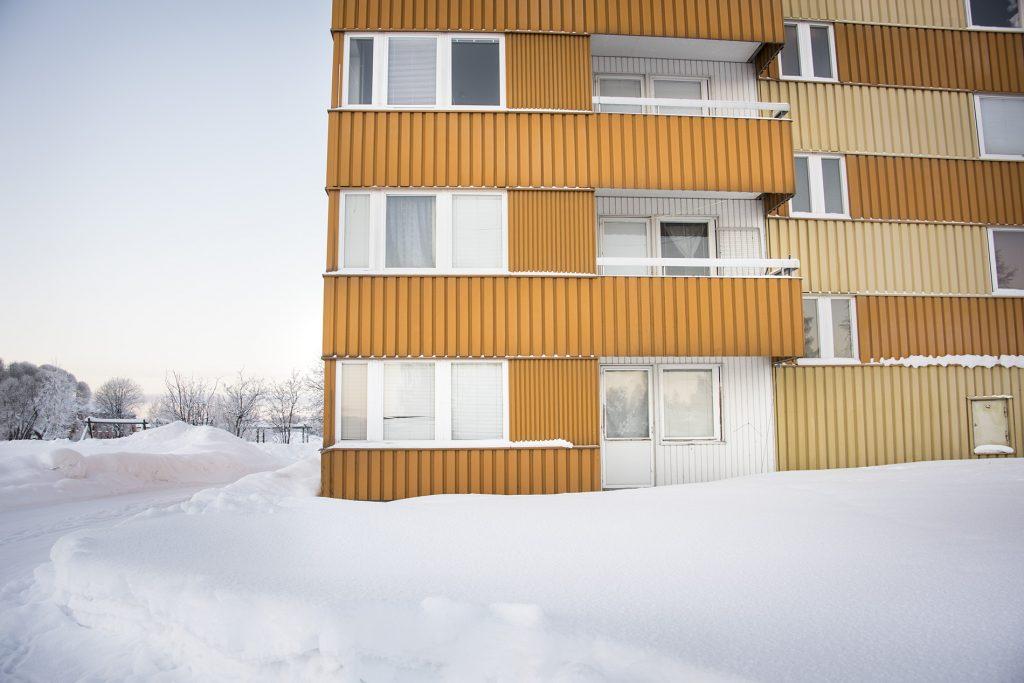 Gult hus fotat utifrån med snö på marken