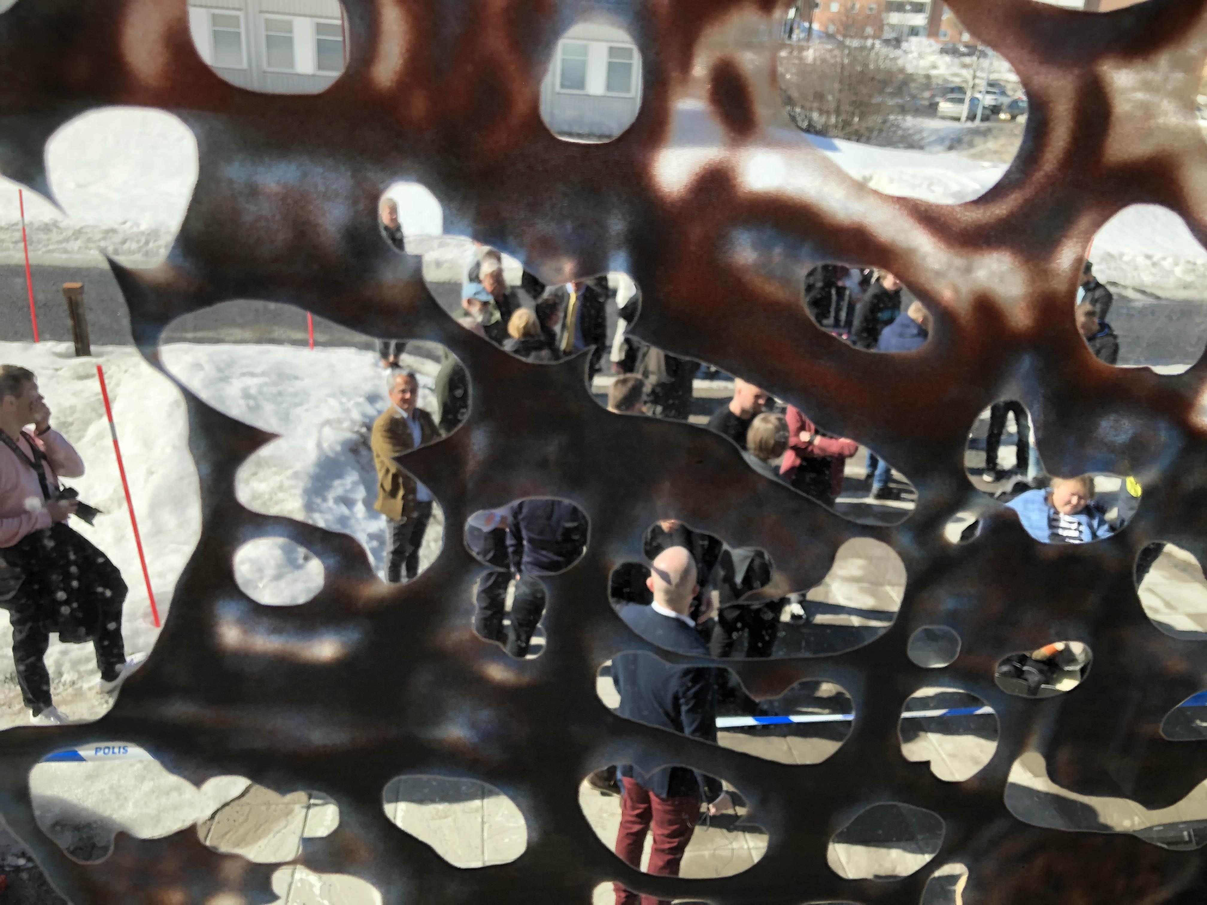 Detalj från glasfasad där man ser människor samlade utanför huset.