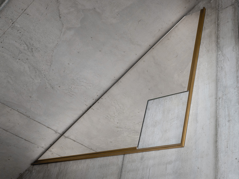 Hängd spegel med fyrkantigt hål i mot betongvägg