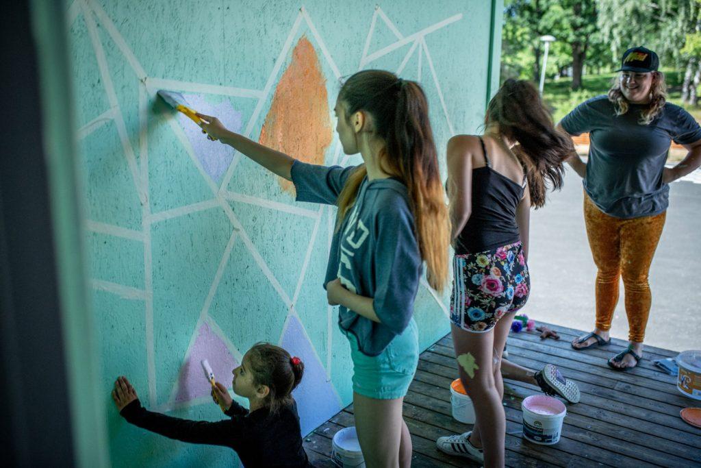 Barn och konstnär målar vägg
