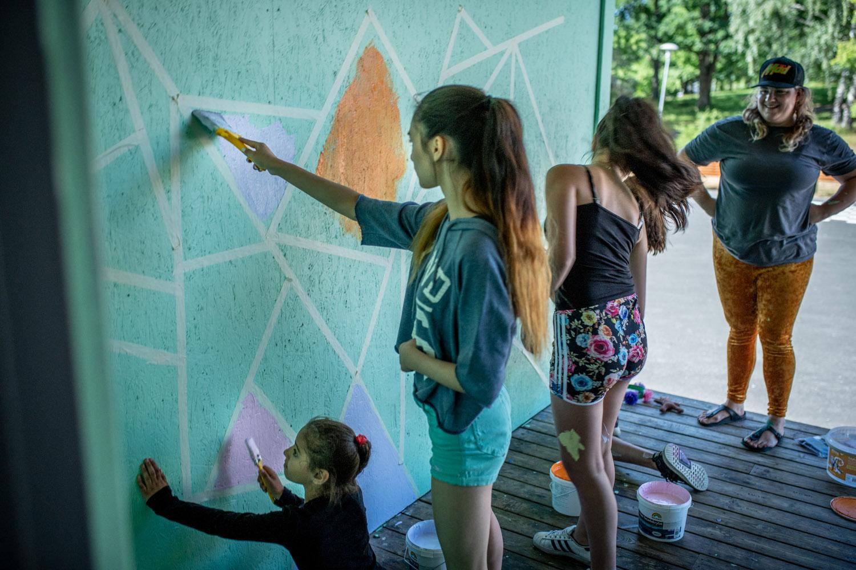 Barn och konstnär målar vägg i grönt, vitt, rosa och orange.