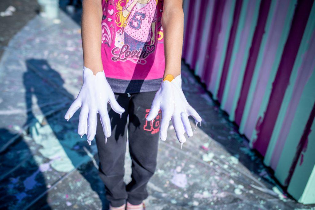 Lila färg droppar från händer