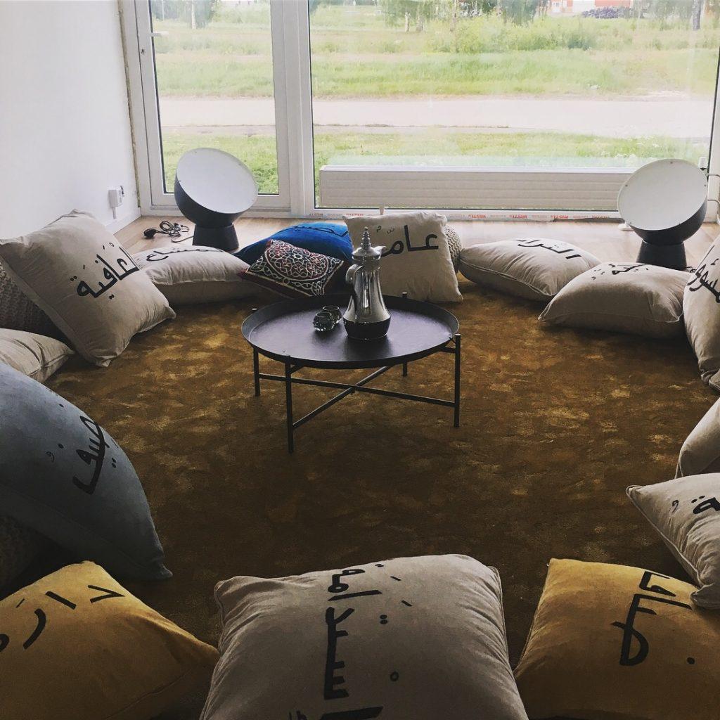 Vardagsrum med kuddar på golvet och dukad bricka.