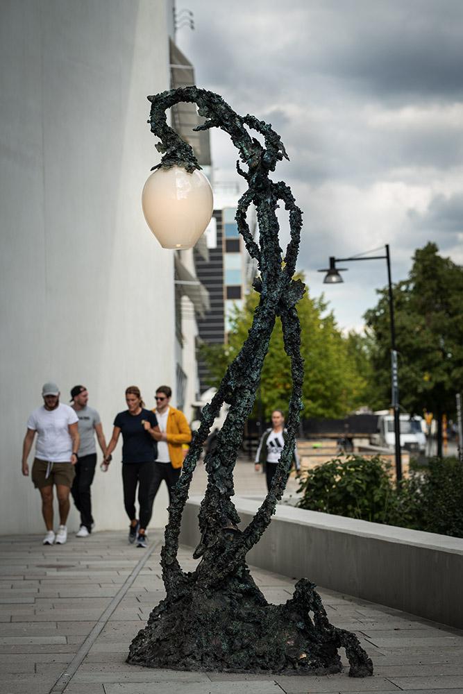 Stående helhetsbild på Lyktan med människor gående mot konstverket.