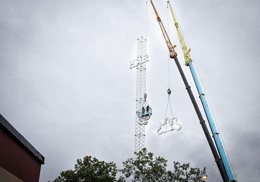 Lyftkran lyfter ljusskyltar hög upp på en stolpe.