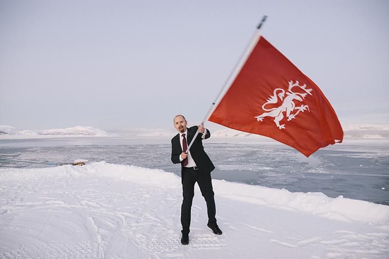 En man i ett snöigt landskap viftar med en röd flagga.