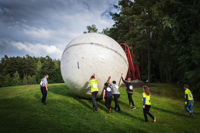 Människor rullar en stor boll på ett fält